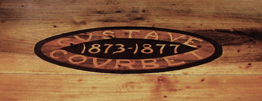 Intarsio sul tavolo personale a cui sedeva Gustave Courbet al Café du Centre.